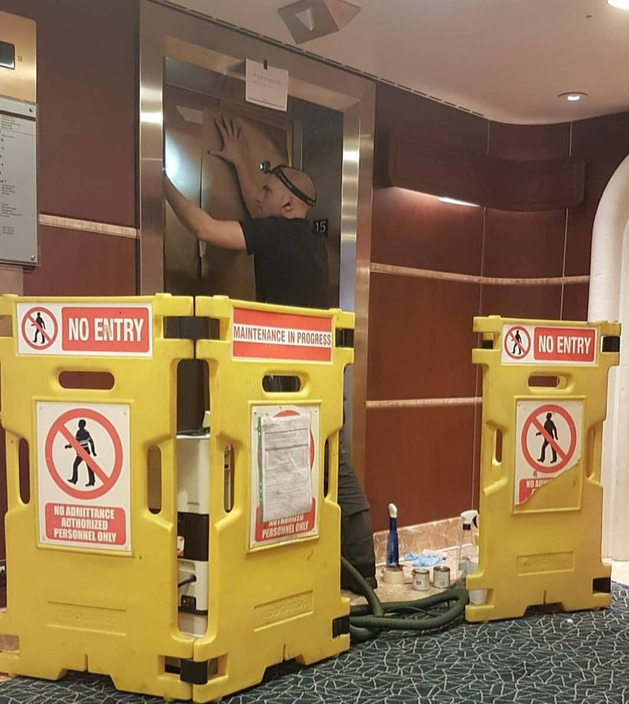 Image Description: 'No Entry' barriers surrounding an out of service lift/elevator. A repair man is trying to fix the lift.