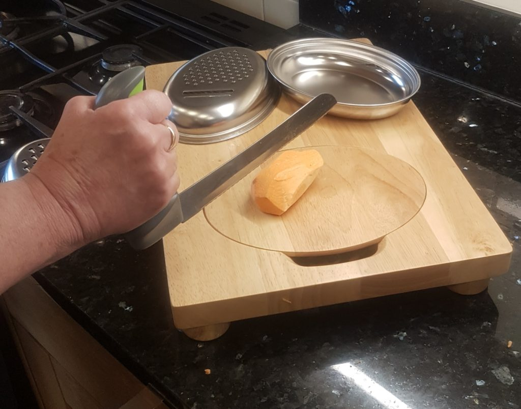 Demonstration of the Easi-Grip knife being used to cut a vegetable on the Easi-Grip food prep board