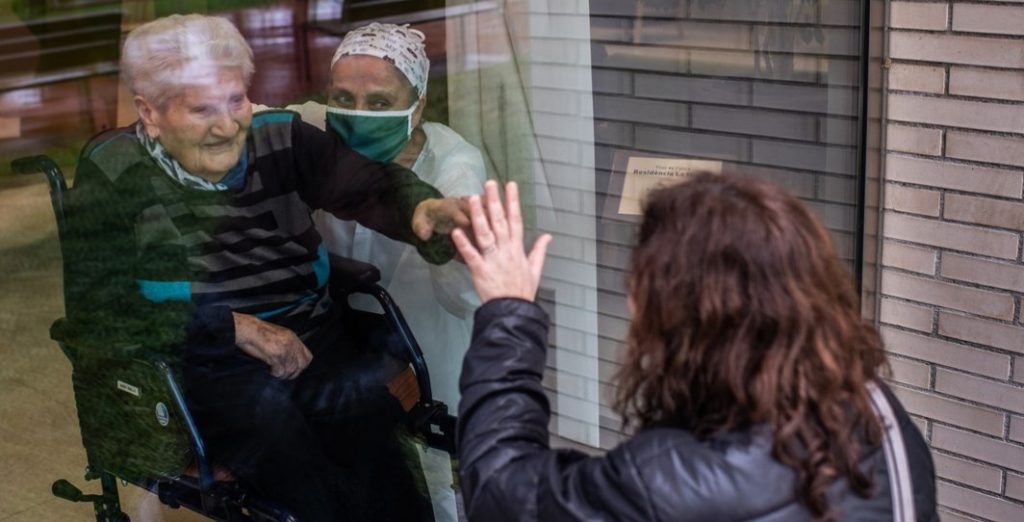 [Image Description: An elderly man in a care home looks out at a female relative from behind a closed window. A carer, wearing a face mask, sits beside the man]